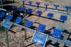 "Photograph showing three rows of blue square solar panels. Panels in left portion are labeled ""cleaned"" and panels in right portion are labeled ""soiled."""