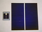 Two deep blue solar cell samples.  Small square cell to left, and larger square cell to right. Each sample is covered by very narrow horizontal lines and one wider vertical line.